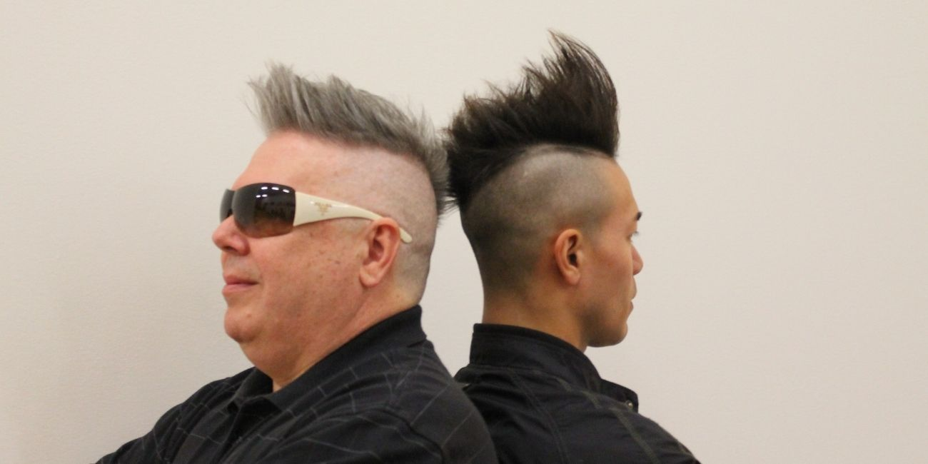 Two men with mohawks stand back to back