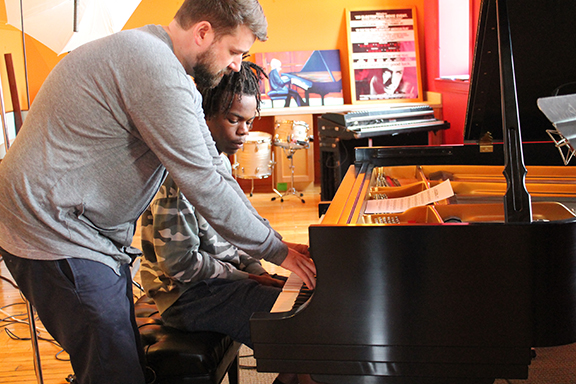 Adam Maness of Open Studio Network teaching Royce Martin on piano