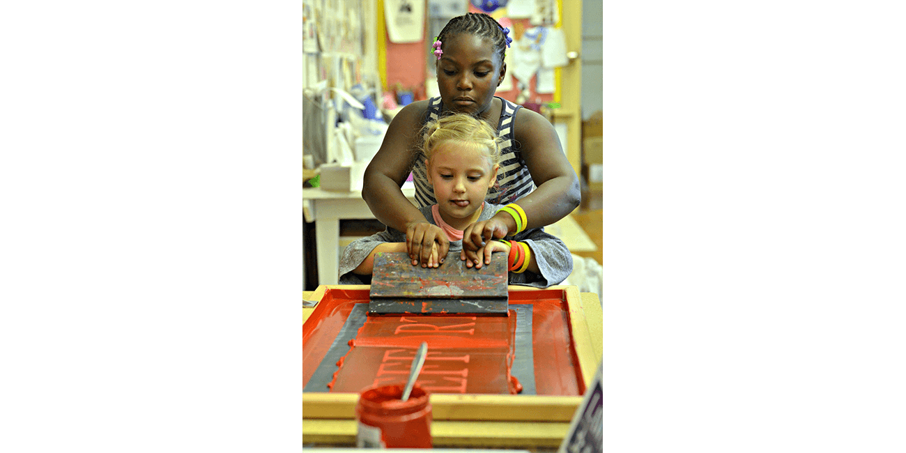 Two students learn to screen print at Intersect Arts Center