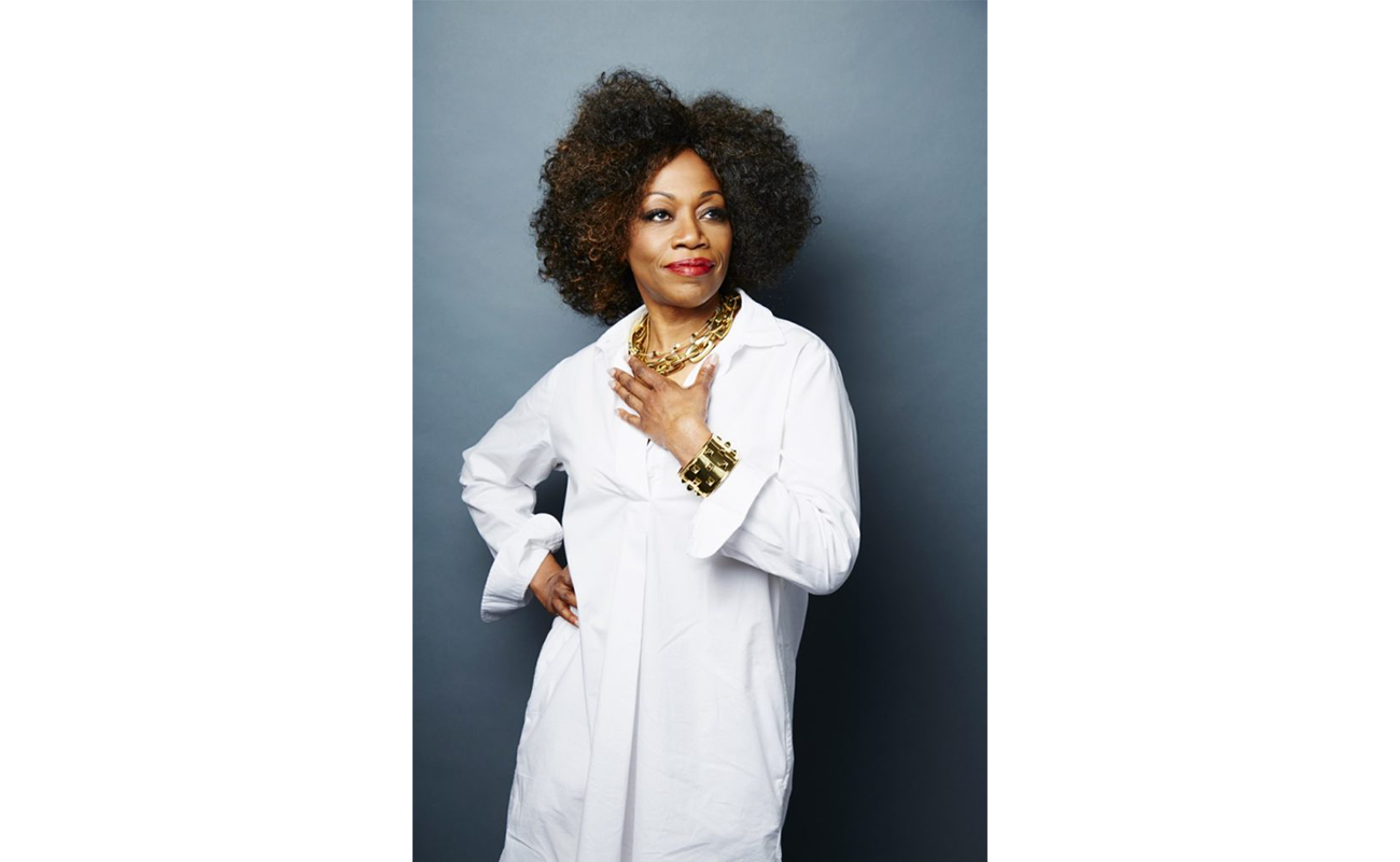 Regina Taylor stands in a white dress, looking away from the camera in front of a blue background with her hand on her chest.
