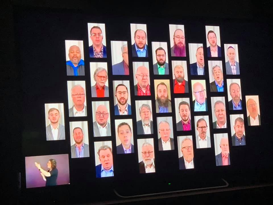 Gateway Men's Chorus singers on a screen in individual rectangles during a concert.